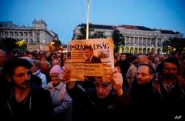 FILE - A man holds up the last printed edition of Nepszabadsag during a demonstration organized to express solidarity with the Hungarian political daily Nepszabadsag in Budapest, Hungary, Oct. 8, 2016.