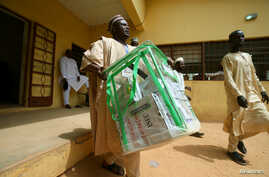 An electoral staff member carries electoral materials outside the Independent National Electoral Commission (INEC) office in Daura, Katsina State, Nigeria, Feb. 22, 2019.