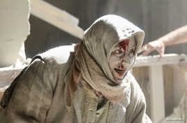 An injured woman reacts at a site hit by airstrikes in the rebel held area of Old Aleppo, Syria, April 28, 2016.