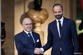 Newly-appointed French Prime Minister Edouard Philippe (R) is greeted by his predecessor Bernard Cazeneuve (L) during a handover ceremony at the Hotel Matignon, in Paris, France, May 15, 2017.