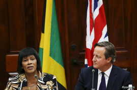 Jamaica's Prime Minister Portia Simpson-Miller (L) addresses the audience as her British counterpart David Cameron looks on during a bilateral meeting at Jamaica House in Kingston, Sept. 29, 2015.