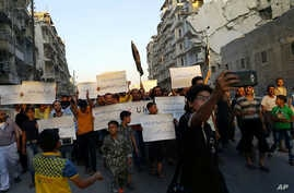 Activists in Syria's besieged Aleppo protest against the United Nations for what they say is its failure to lift the siege off their rebel-held area, Sept. 13, 2016.