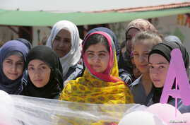Nobel Peace Prize laureate Malala Yousafzai (C) poses with girls for a picture at a school for Syrian refugee girls, built by the NGO Kayany Foundation, in Lebanon's Bekaa Valley, July 12, 2015.