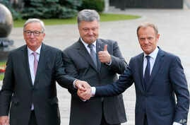 Ukrainian President, Petro Poroshenko, center, European Council President Donald Tusk, right, and European Commission President Jean-Claude Juncker shakes hands during a meeting in Kiev, Ukraine, July 13, 2017.