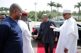 President of Nigeria Muhammadu Buhari (R) greets former President of Ghana John Mahama (2nd R) in Abuja on Jan. 9, 2017, before a meeting on the political situation in Gambia.