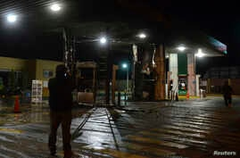 A plainclothes Mexican police officer takes pictures with his cellphone of a gas station following an arson attack in Morelia, Oct. 27, 2013.
