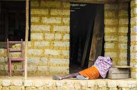 In this Tuesday, Oct. 21, 2014 file photo, a man suffering from the Ebola virus lies on the floor outside a house in Port Loko Community, on the outskirts of Freetown, in Sierra Leone. Ebola surveillance teams are going house-to-house in neighborhood