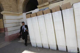 A man walks past rows of election ballot boxes, before they are transported to polling offices, in the premises of the district city court in Karachi May 8, 2013.