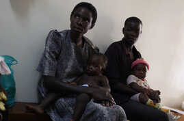 In a photo made Friday, Oct. 30, 2009  mothers with their children suffering from malaria wait to receive a new vaccine at the Walter Reed Project Research Center in Kisumu in Western Kenya.  A new vaccine being tested here is giving the medical comm