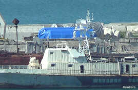 FILE - A still image taken from video footage shows blue tarpaulins covering equipment at the port of Feodosia, Crimea, July 11, 2017.