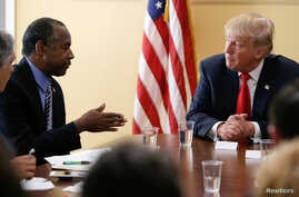 FILE - Republican presidential nominee Donald Trump listens to former presidential candidate Ben Carson during a meetig with local small-business leaders before a campaign rally in West Palm Beach, Fla., Oct. 13, 2016.