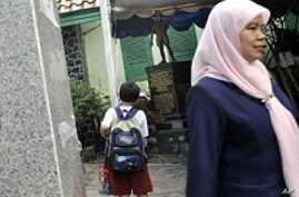 A school official (R) leaves as students look at the newly set-up bronze statue depicting President Obama as a boy at the Menteng One primary school of Jakarta, 22 Feb 2010