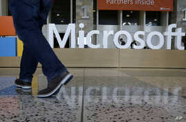 FILE - In this April 28, 2015 file photo, a man walks past a Microsoft sign set up for the Microsoft BUILD conference at Moscone Center in San Francisco. Starting next year, Microsoft will cut the free space it offers through its OneDrive service to