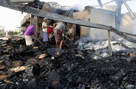 Yemeni men inspect damage at a factory allegedly targeted by Saudi-led coalition airstrikes in the Red Sea town of Hodeidah, July 27, 2018.
