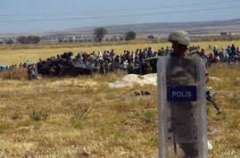 Turkish soldiers stand as people from the Syrian town of Ain al-Arab, or Kobani, wait to cross into Turkey following the attacks by Islamic State militants as seen from the Turkish side of the border in Suruc, Turkey, June 25, 2015.