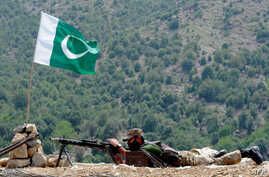 A Pakistani soldier takes position in Manatu mountain at the central part of Kurram Agency, Pakistan's tribal belt bordering Afghanistan, during an operation against militants, July 10, 2011.
