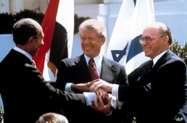 FILE - In this March 26, 1979, file photo, Egyptian President Anwar Sadat, left, U.S. President Jimmy Carter, center, and Israeli Prime Minister Menachem Begin clasp hands on the North lawn of the White House as they completed signing of the peace tr