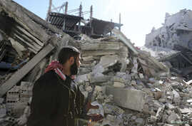 A Free Syrian Army fighter carries his weapon as he walks past damaged buildings in the Arabeen neighborhood of Damascus, Syria, Feb. 12, 2013.