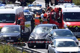 French security forces and emergency vehicles surround a car, center, on a highway between Boulogne-sur-Mer and Calais in northern France that authorities say was used in an attack on soldiers near Paris, Aug. 9, 2017.