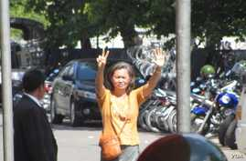 Mu Sochua raises her hands showing seven finger sign representing her party from inside police compound to supporters. (Khoun Theara/VOA)