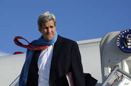 U.S. Secretary of State John Kerry reacts to the blustery weather on arrival in Munich, Germany, Jan. 10, 2015.