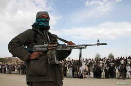 FILE - A member of the Taliban insurgent and other people stand at the site during the execution of three men in Ghazni Province, Afghanistan, April 18, 2015.