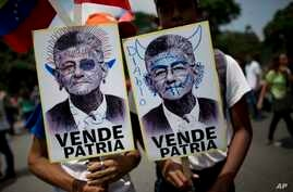 "Government supporters hold defaced pictures of opposition Congressman Henry Ramos Allup, which read in Spanish ""Country seller,"" as they march in Caracas, Venezuela, Sept. 11, 2017. Government supporters marched with pictures of opposition leaders bl"