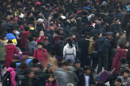 FILE - People rush to catch trains at Beijing station in Beijing, Jan. 8, 2012. The number of the city's permanent residents reached 21.707 million last year, 22,000 fewer than the previous year, Xinhua said.