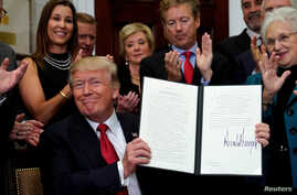 President Donald Trump smiles after signing an executive order to make it easier for Americans to buy bare-bone health insurance plans and circumvent Obamacare rules, at the White House in Washington, Oct. 12, 2017.