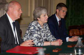 FILE - British Prime Minister Theresa May, center, sits with Gavin Williamson, her new defense secretary, left, and Britain's First Secretary of State Damian Green inside 10 Downing Street, London, June 26, 2017.