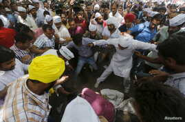Protesters gather around a farmer who hung himself from a tree during a rally organized by AAP, in New Delhi, India, April 22, 2015.