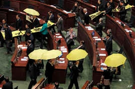 "Pro-democracy legislators hold up yellow umbrellas and banners stating ""I want real universal suffrage"" and ""Leung Chun-ying Step down"" as they walk out of the Legislative Council during Hong Kong Chief Executive Leung Chun-ying's annual policy addre"