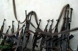 Kalashnikov assault rifles and a couple of heavy machine guns are lines up against a wall at one of Mogadishu four open-air markets, Monday, July 9, 2001.  As the United Nations discusses what to do about the world's illegal small arms trade, it is b