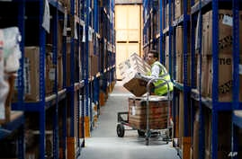 Lovespace warehouse worker Pawel Mazur unloads boxes from a trolley to place them into their allocated zones at the warehouse in Dunstable, England, Jan. 14, 2019.