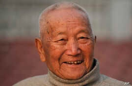 FILE - Nepalese mountain climber Min Bahadur Sherchan, 85, smiles as he finishes his morning yoga workout at his residence in Kathmandu, Nepal, April 12, 2017. Officials said Sherchan died May 6.