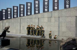 """FILE - Chinese military band members leave near banners with the words reading """"National Memorial"""" after a ceremony to mark China's first National Memorial Day at the Nanjing Massacre Memorial Hall in Nanjing in eastern China's Jiangsu province."""