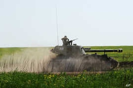 An armored Russian vehicle rides during a training exercise at the Kuzminsky military training ground outside the village of Chkalovo near the Russian-Ukrainian border, in the Rostov region, Russia, May 25, 2015.