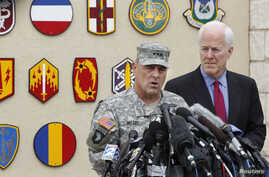 Fort Hood base commander Lieutenant General Mark Milley speaks during a news conference while flanked by U.S. Senator John Cornyn (R-TX) at the entrance to the army base in Texas April 3, 2014