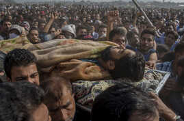 Kashmiri men carry the body of Mohammad Saleem Malik, a civilian during his funeral procession in Srinagar, Indian controlled Kashmir, Sept. 27, 2018. Residents say Malik was killed by Indian troops during an anti militancy operation in Srinagar.