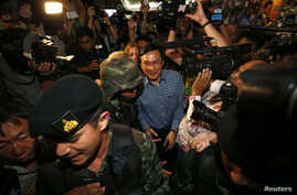 Former Thai Education Minister Chaturon Chaisang (C), who had been on the run after refusing to turn himself in to the military after being summoned, is surrounded by soldiers and reporters as he is being detained after giving a talk at the Foreign C