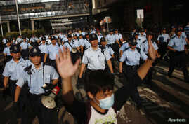 A protester raises his arms as police officers try to disperse a crowd near government headquarters in Hong Kong, Sept. 29, 2014.
