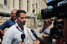 Lebanese father Ali al-Amin speaks to journalists after dropping charges against his estranged wife and an Australian TV crew for attempting to kidnap their children, in front of the courthouse, in the Beirut southeastern suburb of Baabda, Lebanon, W