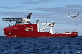 In this April 9, 2014 photo provided by the Australian Defense Force, a Royal Australian Air Force AP-3C Orion flies past Australian Defense vessel Ocean Shield on a mission to drop sonar buoys to assist in the acoustic search of the missing Malaysia...
