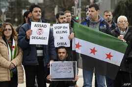 "Demonstrators holding a Free Syria flag and placards reading ""Stop the killing in Syria"" take part in a protest outside the United Nations (UN) offices in Geneva, on Jan. 29, 2016 on the opening day of Syrian peace talks."