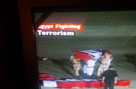 An Egyptian government channel broadcasts an honor guard carrying the casket of a slain policeman with 'Egypt Fighting Terrorism' banner on screen, August 8, 2013.