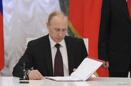 Russian President Vladimir Putin prepares to sign a law on ratification of a treaty making Crimea part of Russia, during a ceremony in Moscow's Kremlin in Moscow, March 21, 2014.