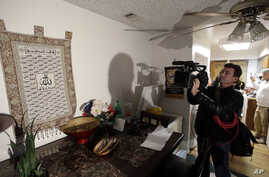 A member of the media films a wall tapestry displaying religous writing in the living room of an apartment in Redlands, Calif., shared by San Bernardino shooting rampage suspects Syed Farook and his wife, Tashfeen Malik, Friday, Dec. 4, 2015.