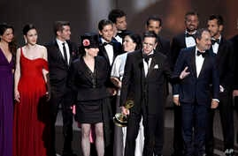 "Amy Sherman-Palladino, front and center left, Daniel Palladino and the cast and crew of ""The Marvelous Mrs. Maisel"" accept the award for outstanding comedy series at the 70th Primetime Emmy Awards, Sept. 17, 2018, at the Microsoft Theater in Los Ange"