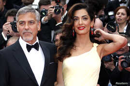 """FILE - Cast member George Clooney and his wife Amal pose on the red carpet as they arrive for the screening of the film """"Money Monster"""" out of competition during the 69th Cannes Film Festival in Cannes, France."""