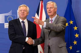 FILE - EU chief Brexit negotiator Michel Barnier, right, welcomes British Secretary of State David Davis for a meeting at the EU headquarters in Brussels, July 17, 2017. The British government is fighting back against criticisms that it is divided an